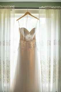 hanged white applique corset wedding gown in between white window curtain inside room
